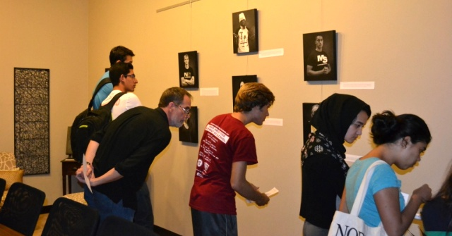 Members of the Westminster Community examine pictures from the photo exhibit.